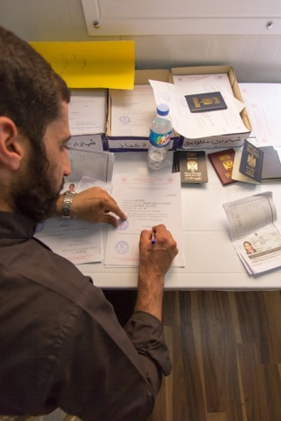Priest Signing Documents For Refugees In Iraq