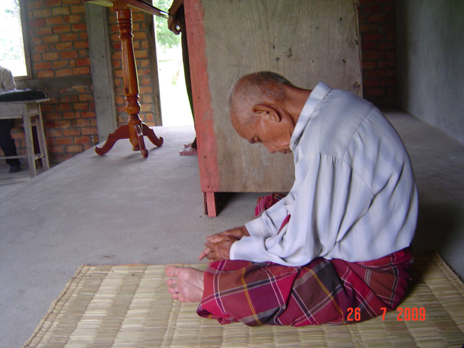 Photo of a man from Laos praying in spite of Christian persecution.