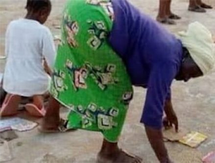 Seeing this Nigerian woman rake the ground for relief scraps should shake us all